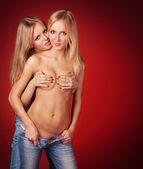 Two cute topless girls covering and hugging over red background — Stock Photo
