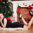Happy woman laying on the floor in Front Of Christmas Tree — Stock Photo