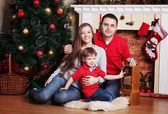 Happy family in Front Of Christmas Tree — Stock Photo