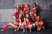 Seven Cute go-go sexy girls in red racing costume — Stock Photo