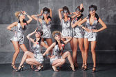 Group of seven happy cute girls in silver go-go costume ready to — Stock Photo