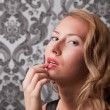 Beautiful blond woman with finger on her lips — Stock Photo #9248565