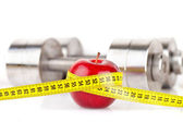 Dumbbells with an apple — Stock Photo