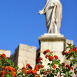 Blured Statue with Red flowers at the forefront — Stock Photo