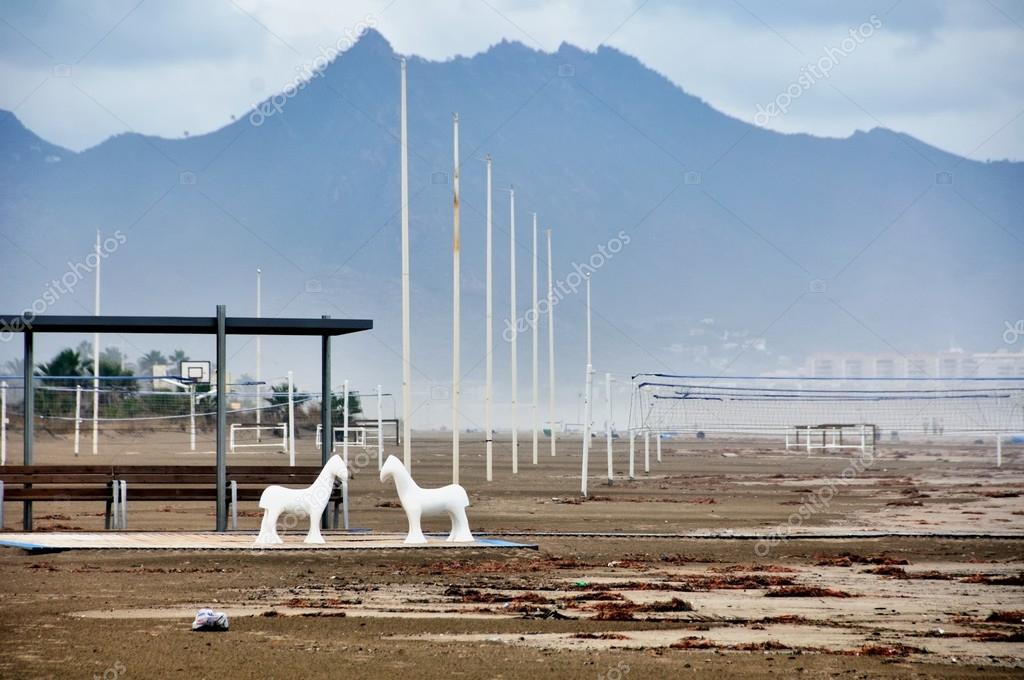 Plastic horses standing at the beach of Castellon de la Plana, Spain. Desert de les Palmes mountains at the background. — Stock Photo #21234615