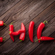 Chili sign with fresh chillies on a wooden table — Stock Photo