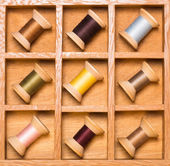 Wooden shadow box with thread spools — Stock Photo