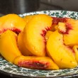 Sliced peaches in bowl on table — Stock Photo #12893753