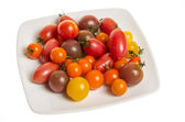 Fresh mixed tomatoes on plate — Stock Photo