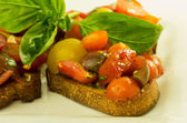 Fresh bruschetta with mixed tomatoes cheese and basil — Stock Photo