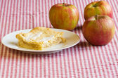 Apple pie on white plate with apples — Stock Photo