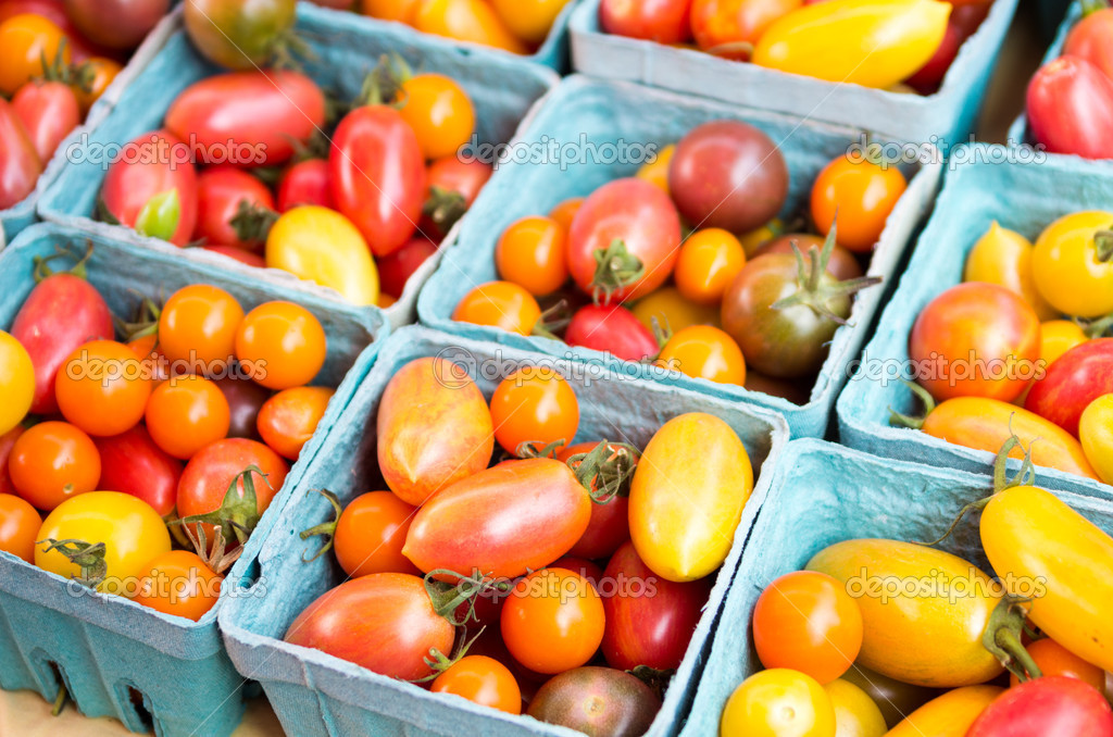 Baskets of colorful cherry tomatoes on display at the market — Stock Photo #13200369
