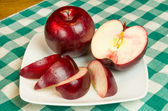Rome Beauty apple slices on white plate — Stock Photo