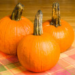 Three orange pumpkins on a wooden table — Stock Photo