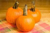 Three orange pumpkins on a wooden table — Stock Photo