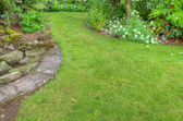 Landscaped garden scene with stone edging — Stock Photo