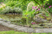 Landscaped garden scene with stone edged pond — Stock Photo