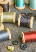 Buttons and spools of thread with needle — Stock Photo