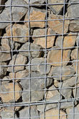 Wire mesh and stone retaining wall — Stock Photo