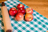 Red apples and rolling pin — Stock Photo