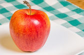Gala apple on a white plate — Stock Photo
