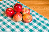 Fresh red apples on checked cloth — Stock Photo