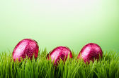 Three pink foil Easter eggs on grass — Stock Photo