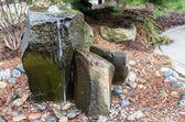 A rocky bubbling water fountain in a courtyard garden — Stock Photo