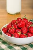 Bol de fraises avec une bouteille de lait — Photo