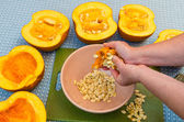 A cook extracting the seeds from a pumpkin — Stock Photo