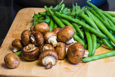 Mushrooms and green beans on a wooden board — Stock Photo
