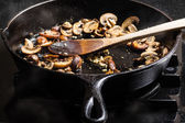 Sauteing sliced mushrooms in a skillet — Stock Photo