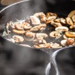 Sauteing sliced mushrooms in skillet — Stock Photo #37988727