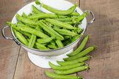 Fresh peas in a white colander — Stock Photo