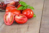 Fresh red paste tomatoes with jar — Stock Photo