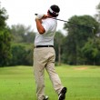 Asian Male golf player teeing off golf ball from tee box — Stock Photo #18436771
