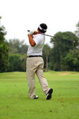Asian Male golf player teeing off golf ball from tee box — Stock Photo