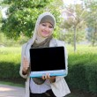 Stock Photo: Young muslim womin head scarf shown laptop and thumb up