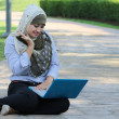 Stock Photo: Beautiful young Muslim girl with surprise emotion and laptop