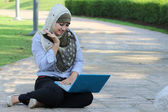 Beautiful young Muslim girl with surprise emotion and laptop — Stock Photo