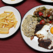Stock Photo: Steaks and eggs with mushroom sauce and fries