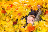 Girl and maple leaves — Stock Photo