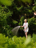 Woman and garden hose — Foto Stock