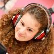 Stock Photo: Girl listening to music on computer