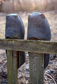 Old galoshes on the fence — Stock Photo