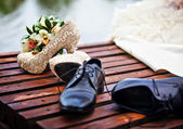 Wedding shoes on the bridge near the water — Stock Photo