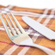 Knife and fork on a napkin — Stock Photo #17938185