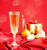 Copa de champaña contra adornos navideños — Foto de Stock