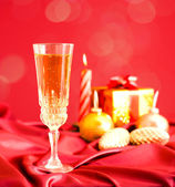 Glass of champagne against Christmas decorations — Stok fotoğraf