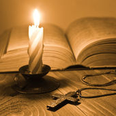 Metal cross with book and candle — Stock Photo